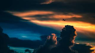 plane flying in the sky, with cloouds and sun setting