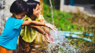 children playing with running water