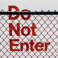 do not enter sign behind a fence