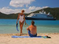 couple on beach with cruise ship in the background